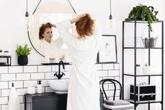 Kvinna framme av spegeln i minsta badruminre med affischen, stol och växter Verkligt foto royaltyfri foto