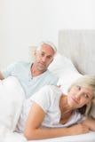 Kvinna förutom man i säng hemma Fotografering för Bildbyråer