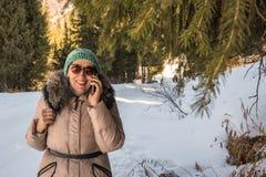 Kvinna 50 gamla år med mobilen i vinter på naturen Royaltyfri Foto