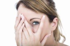 Kvinna generat blygt kika till och med fingrar Arkivfoton