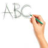Kvinna hand som rymmer en blyertspenna och skriver ABC Royaltyfri Bild