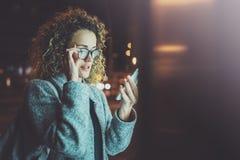 Kvinna i ögonexponeringsglas som rymmer handsmartphonen i atmosfärisk stad för natt Kvinnlighänder genom att använda mobiltelefon Royaltyfria Bilder