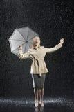 Kvinna i överrock med paraplyet som tycker om regnet royaltyfri foto