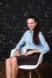 Kvinna i affärsklädsammanträde på stol och att le Arkivfoton
