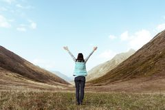 Kvinna i armar för en bergdal som lyfts i begreppet för himmellopplivsstil av aktiva ferier för framgångaffärsföretagaffärsföreta royaltyfria bilder