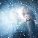 Kvinna, i att blåsa silke på en snöig bakgrund royaltyfri foto