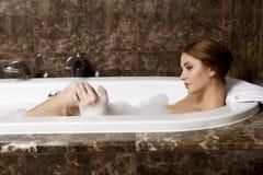Kvinna, i att koppla av för bad. Closeup av den unga kvinnan i badkarbathin Royaltyfri Fotografi