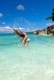 Kvinna i att vinka för hav och plaskande vatten Fotografering för Bildbyråer