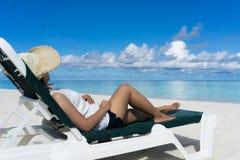 Kvinna i avkoppling på den tropiska stranden Arkivfoto