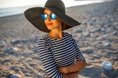 Kvinna i avriven klänning med en hatt på stranden arkivfoton