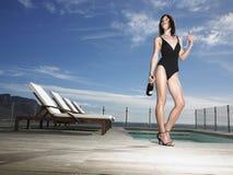 Kvinna i baddräkt med Champagne Bottle By Pool Royaltyfri Foto