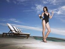 Kvinna i baddräkt med Champagne Bottle By Pool Fotografering för Bildbyråer
