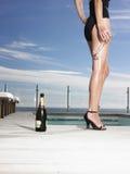 Kvinna i baddräkt med Champagne By Pool Fotografering för Bildbyråer