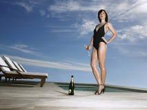 Kvinna i baddräkt med Champagne By Pool Arkivfoto