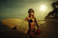 Kvinna i baddräkten som rymmer en surfingbräda Fotografering för Bildbyråer