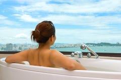 Kvinna i badkaret som ser havssikt Royaltyfri Fotografi