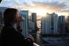 Kvinna i badrock som dricker hennes morgonkaffe eller te på en i stadens centrum balkong Härlig soluppgång i i stadens centrum mi arkivbild