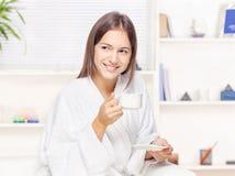 Kvinna i badrock som hemma kopplar av Arkivfoto