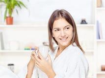 Kvinna i badrock som hemma kopplar av Arkivfoton