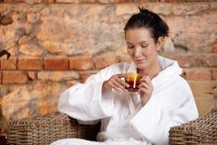 Kvinna i badrock som tycker om tea Royaltyfri Foto