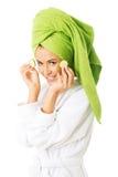 Kvinna i badrocken som applicerar gurkan på ögon Royaltyfri Fotografi