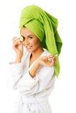 Kvinna i badrocken som applicerar gurkan på ögon Arkivbilder