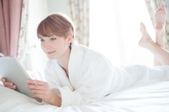 Kvinna i badrocken som ligger på en säng Arkivfoton