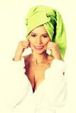 Kvinna i badrocken som rymmer hennes mun i ett leende Arkivfoton