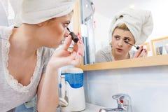 Kvinna i badrummet som applicerar mascara p? ?gonfrans royaltyfri foto
