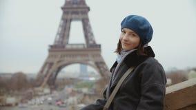 Kvinna i basker och vinterlaget som poserar och ler nära Eiffeltorn i Paris arkivfilmer