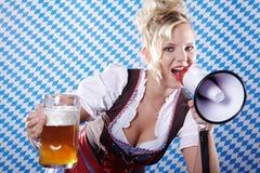 Kvinna i bayersk dräkt och megafon och öl Royaltyfri Foto