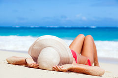 Kvinna i bikini- och sugrörhatten som ligger på tropiskt Royaltyfri Fotografi