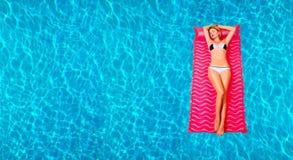 Kvinna i bikini på den uppblåsbara madrassen i simbassängen Arkivbilder