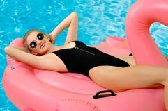 Kvinna i bikini på den uppblåsbara madrassen i simbassängen royaltyfria bilder