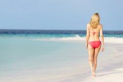 Kvinna i bikini som går på den härliga tropiska stranden Royaltyfri Foto
