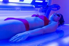 Kvinna i bikini som garvar i wellnessbrunnsort Arkivfoto