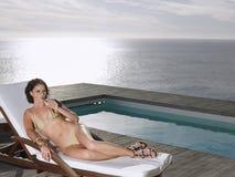 Kvinna i bikini som läppjar Champagne At Poolside By Ocean Arkivfoton
