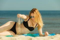 Kvinna i bikini som solbadar och kopplar av på stranden Arkivfoton