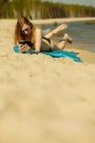 Kvinna i bikini som solbadar och kopplar av på stranden Arkivbilder