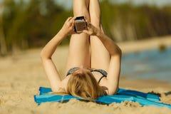 Kvinna i bikini som solbadar och kopplar av på stranden Arkivfoto