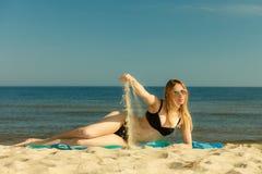 Kvinna i bikini som solbadar och kopplar av på stranden Arkivbild