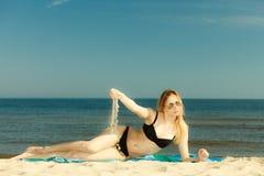 Kvinna i bikini som solbadar och kopplar av på stranden Royaltyfri Bild