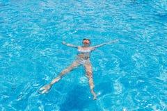 Kvinna i bikini som svävar på baksida i simbassäng Arkivbilder