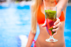Kvinna i bikinihand med mojito för jordgubbe för coctailexponeringsglas nära Royaltyfria Foton