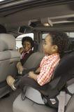 Kvinna i bil med den lilla pojken i förgrund Royaltyfri Bild