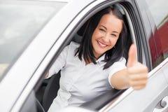 Kvinna i bil- och visningtummarna upp Fotografering för Bildbyråer