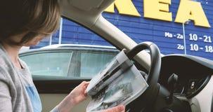 Kvinna i bil som framme läser den IKEA tidskriftkatalogen av lagret stock video