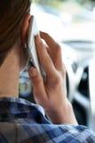 Kvinna i bil som talar på mobiltelefonstundkörning arkivfoto