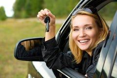 Kvinna i bilen som visar tangenterna Arkivfoto