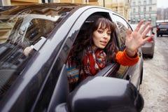 Kvinna i bilhälsning Fotografering för Bildbyråer
